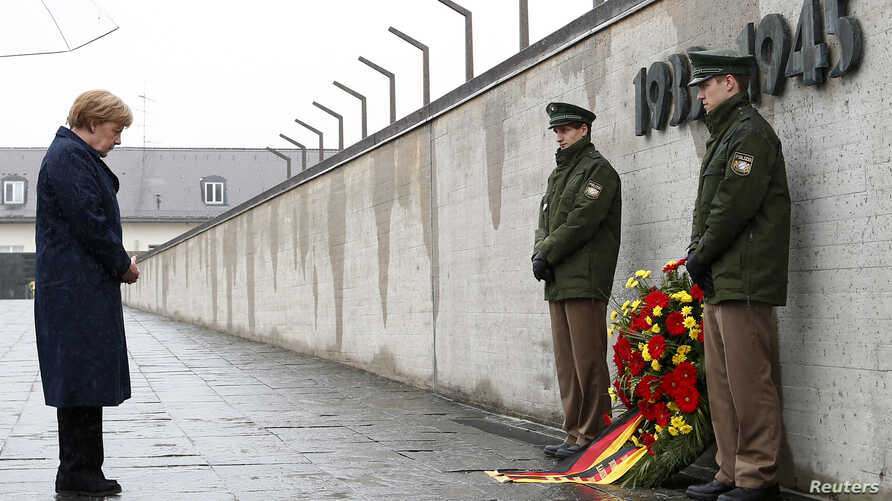 FILE - German Chancellor Angela Merkel observes a moment of silence as she lays a wreath at the memorial in the former German Nazi concentration camp in Dachau to mark the 70th anniversary of the liberation of the camp.