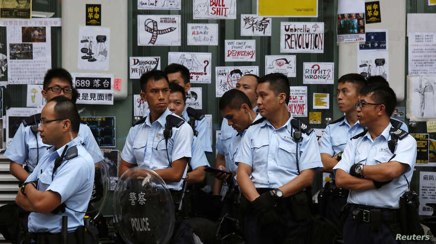 Policemen stand in front of messages left by pro-democracy protesters outside a HSBC branch off a blocked road at Mongkok shopping district in Hong Kong, Oct. 17, 2014.