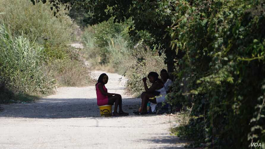 Three young women from Benin City wait in the shade of a lane for clients on the outskirts of Pozuuli near Castel Volturno. The girls said they had been in Italy for two years. (J. Dettmer/VOA)