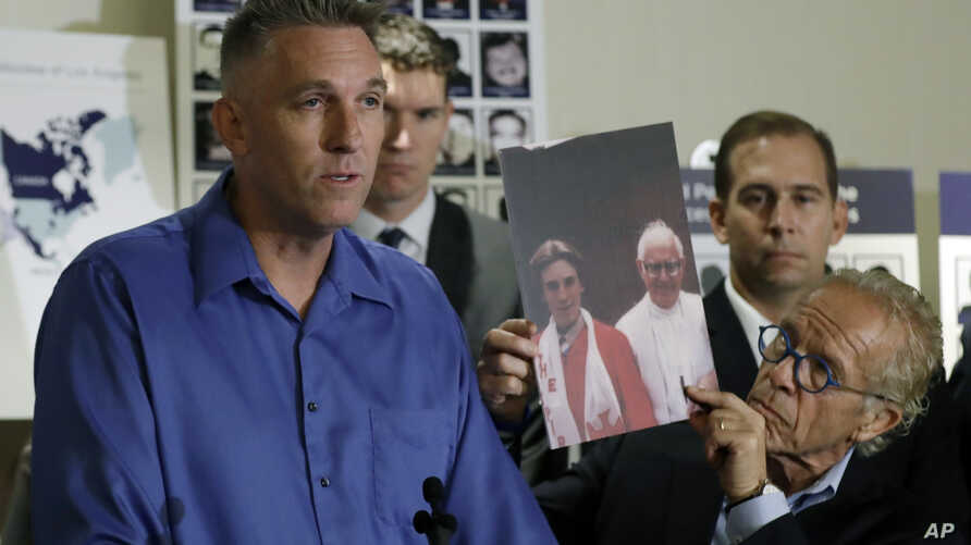 Tom Emens, left, who was sexually abused by a priest, speaks on his experience next to attorney Jeff Anderson, Tuesday, Oct. 2, 2018, in Los Angeles.