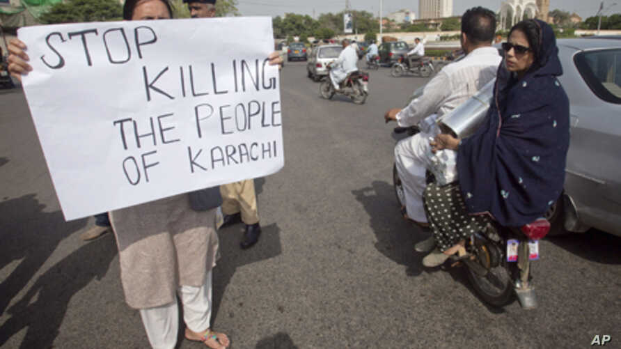 A family rides past on a motor bike as an activist of the civil society group Karachi Concerned Citizen Forum holds a placard along a road in Karachi August 20, 2011.