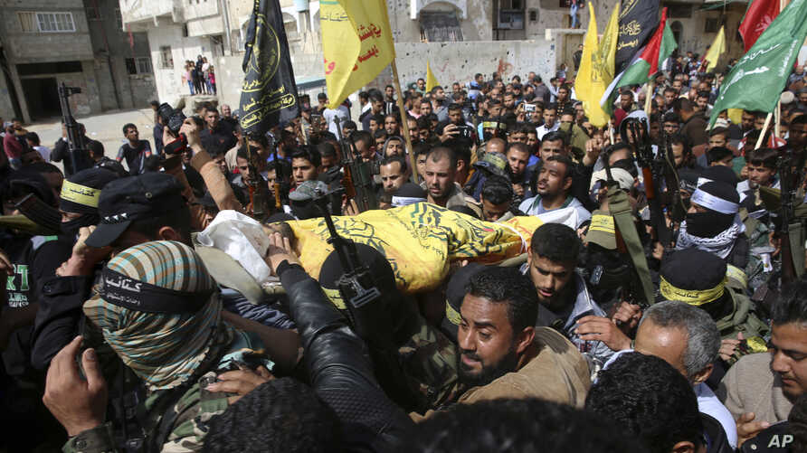 Relatives and masked Palestinian militants carry the body of Hamdan Abu Amsha, 23, during his funeral in Beit Hanoun, Gaza Strip, March 31, 2018.