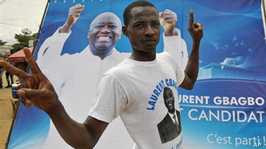 A supporter poses by a poster of Ivory Coast President Laurent Gbagbo in Abidjan, 16 Oct 2009