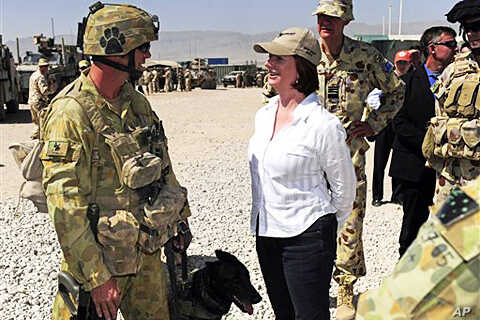 Australian Prime Minister Julia Gillard, center, meets Corporal Craig Turnball and his Explosive Detection Dog during her visit at Multinational Base Tarin Kot in southern Afghanistan, 02 Oct. 2010