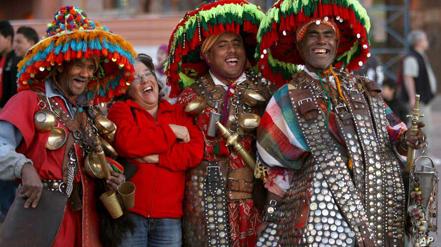 FILE - A Spanish tourist, second from left, jokes as she poses with water sellers in original outfits on the Jamaa El Fanaa square in Marrakesh, Morocco, March 23, 2008.