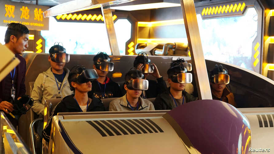 """Staff members wearing virtual reality goggles sit in a motorized cart while performing an inspection of the attraction """"Fly Over Guizhou,"""" at the Oriental Science Fiction Valley theme park in Guiyang, Guizhou province, China, Nov. 16, 2017."""