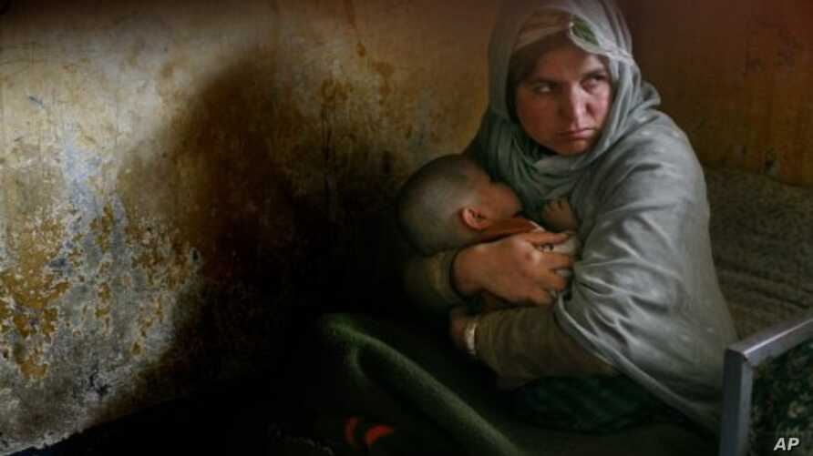 Habiba, who has completed three years of a 10-year prison sentence for murder, holds her daughter Nazanin who was born in jail three years ago but still cannot walk, as they rest in their bunk bed inside Pul-e Charkhi prison in Kabul, Afghanistan. (F