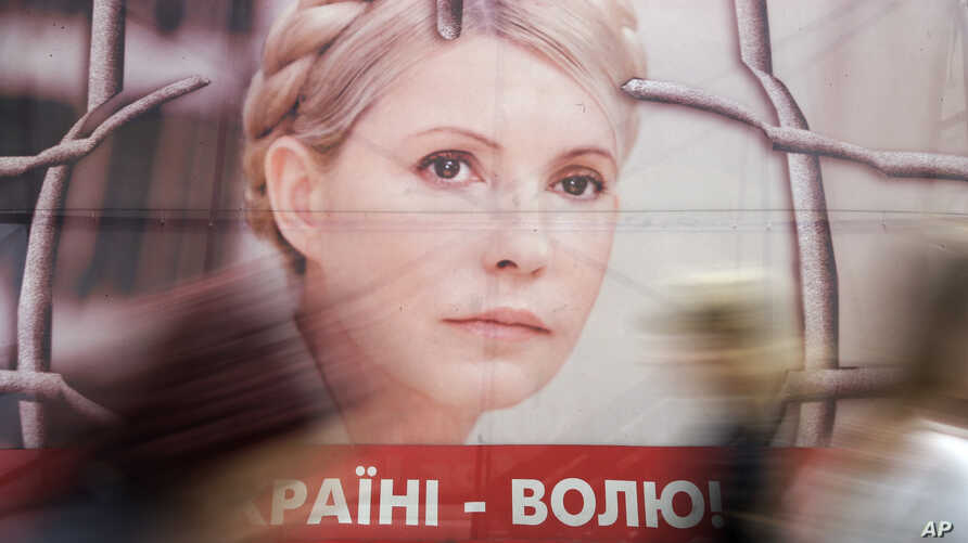 People pass by a poster of Ukraine's imprisoned former Prime Minister Yulia Tymoshenko at a tent camp of her supporters in central Kiev, Ukraine, April 30, 2013.