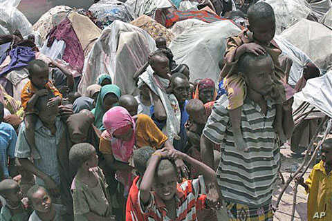Somalis displaced by drought wait outside their makeshift shelters where tens of thousands have arrived in recent months desperately seeking food, water, shelter and other assistance, in Mogadishu, Somalia, July 25, 2011