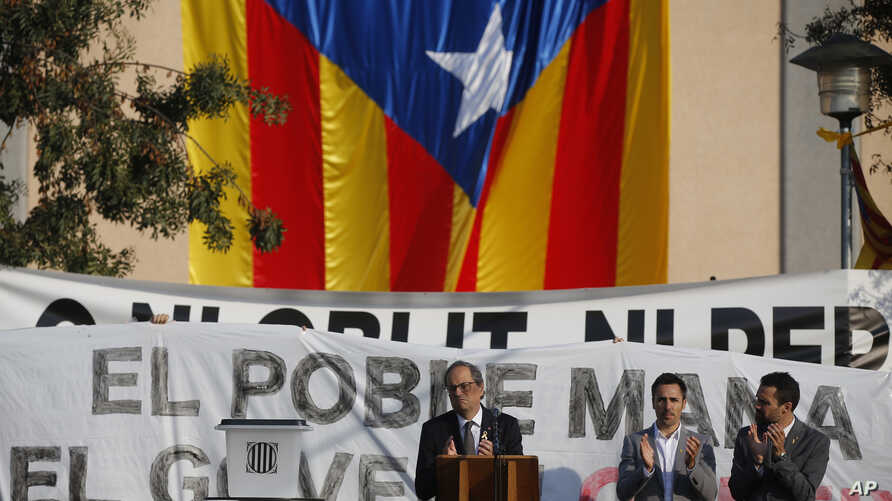 Catalan regional President Quim Torra, centre, applauds in front of a large Catalonia independence flag during a rally in Sant Julia de Ramis, Spain, Monday Oct. 1, 2018.