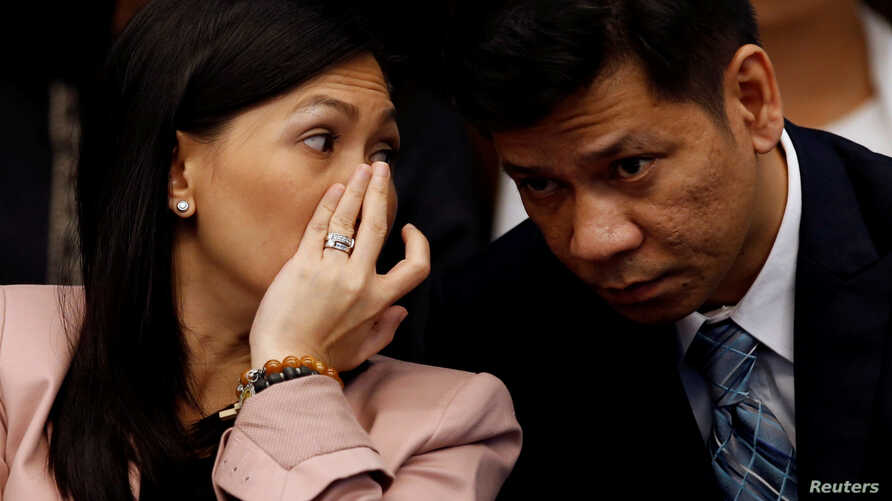FILE - Maia Santos Deguito, a branch manager of the Rizal Commercial Banking Corp (RCBC) whispers to her lawyer as she testifies during a Senate hearing on the money laundering involving $81 million stolen from Bangladesh central bank, at the Philipp