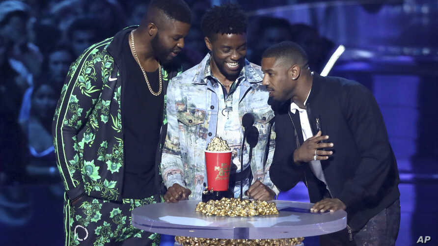 """In this Saturday, June 16, 2018, photo, Winston Duke, from left, Chadwick Boseman and Michael B. Jordan accept the award for best movie for """"Black Panther"""" at the MTV Movie and TV Awards in Santa Monica, Calif."""