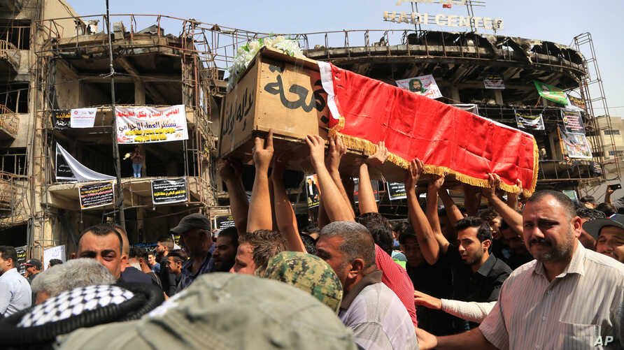 Mourners carry the Iraqi flag-draped coffin of, Akram Hadi, 24, in a Sunday massive truck bomb attack in the Karada neighborhood of Baghdad, Iraq, July 5, 2016.