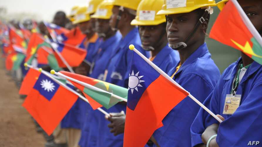 FILE - Students at the vocational training center of reference (Centre de formation professionnelle de reference de Ziniare (CFPR-Z)) in Ziniare, 35kms of Ouagadougou hold Taiwan's and Burkina Faso's flags during the visit of Taiwan's President on Ap