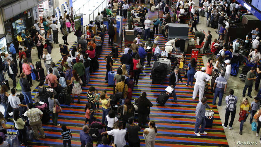 (File) Passengers line up for the security checkpoint at Simon Bolivar airport in La Guaira, outside Caracas.