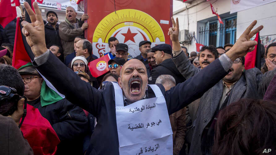 Tunisian workers stage a protest in front of the national union headquarters in the capital Tunis, Jan. 17, 2019.