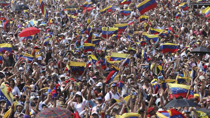 Concert goers unfurl their Venezuelan flags during the Venezuela Aid Live concert on the Colombian side of the Tienditas International Bridge near Cucuta, Colombia, on the border with Venezuela, Feb. 22, 2019.