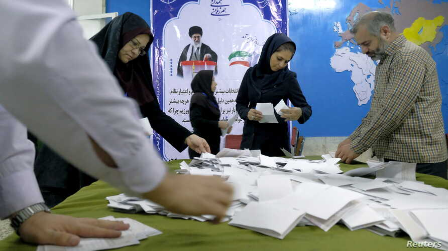 Election officials count ballot papers after the close of polling stations during elections for the parliament and a leadership body called the Assembly of Experts, which has the power to appoint and dismiss the supreme leader, in Tehran, Feb. 26, 20