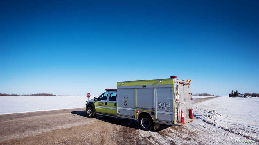 An emergency vehicle blocks the road to traffic the day after a bus carrying the Humboldt Broncos junior hockey team collided with a semitrailer near Tisdale, Saskatchewan, April 7, 2018.