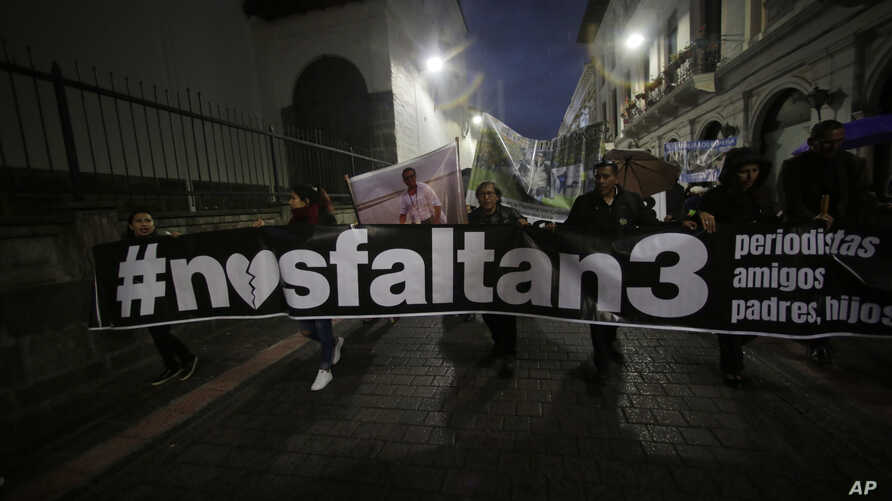 """Relatives of the El Comercio journalists, who were kidnapped on the Ecuador-Colombia border 11 days ago, carry a banner reading in Spanish """"We lack 3"""" and walk to government palace to demand more action by government to secure their release in Quito,"""