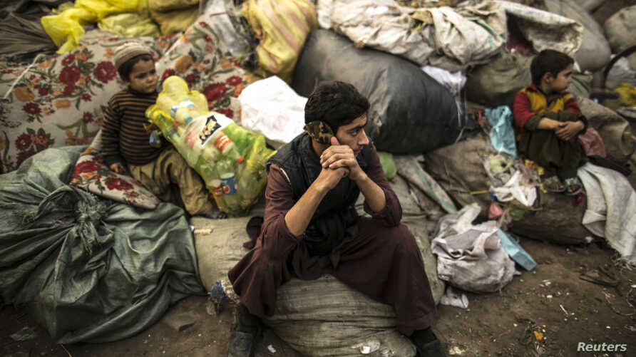 FILE - Afghan refugees sit on sacks filled with used plastic items to sell at their makeshift shelter in a slum on the outskirt of Lahore, Jan. 12, 2015.