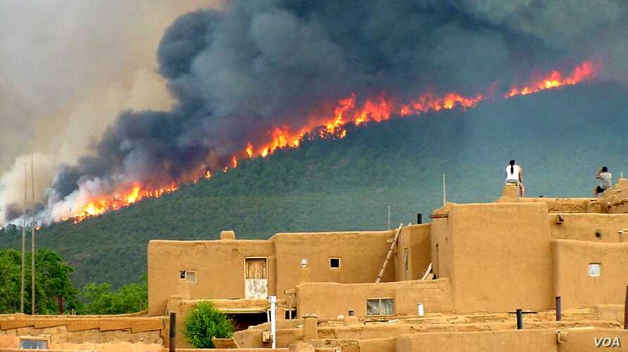 Pueblo tribal members watch the Encebado Fire on Taos Pueblo land in New Mexico, July, 2003.  The fire, sparked by lightening, burned 5,000 acres near the Pueblo, leading to subsequent flooding and erosion when rain finally fell. Photo by Ignacio Per