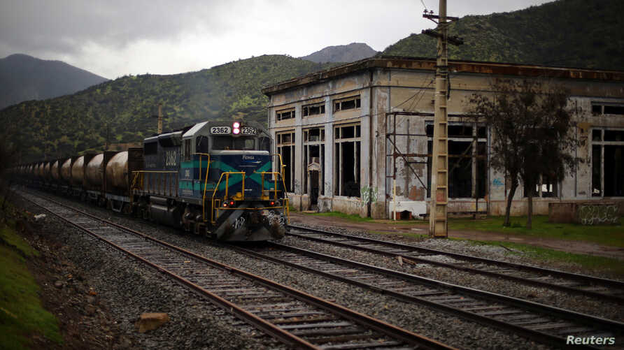 A train transporting garbage rides to a waste dump passing next to an abandoned power plant in Til Til, Chile, Aug. 10, 2017.