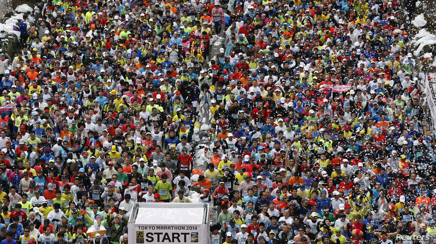 FILE - Runners fill the street at the start of the Tokyo Marathon, February 2014.