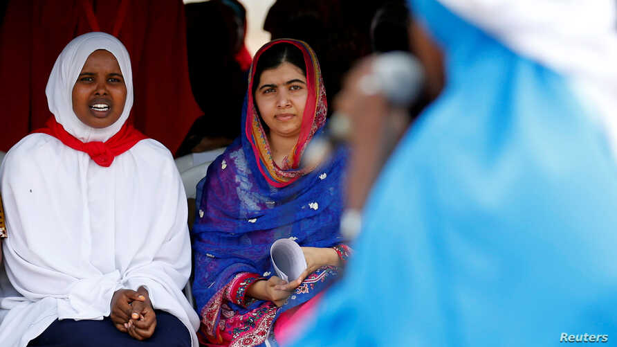 Pakistani Nobel Peace Prize laureate Malala Yousafzai, center, and Somali refugee Rahma Noor attend celebrations to mark Malala's 19th birthday at the Dadaab refugee camp near the Kenya-Somalia border, July 12, 2016.