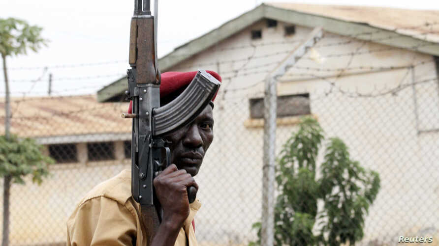 FILE - A prison officer, armed with a rifle, stands guard at Lira Central Prison in northern Uganda, Feb. 13, 2013.