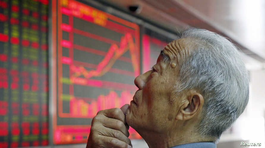 File - An investor watches an electronic board showing stock information at a brokerage office in Beijing, China, July 2015.