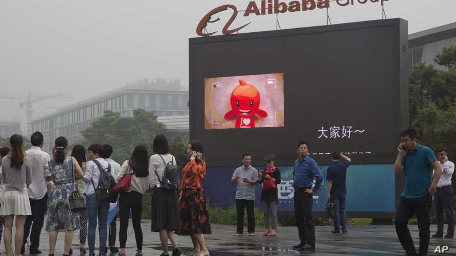 Visitors walk past a giant display at the  Alibaba Group headquarters in Hangzhou, in eastern China's Zhejiang province, May 27, 2016.
