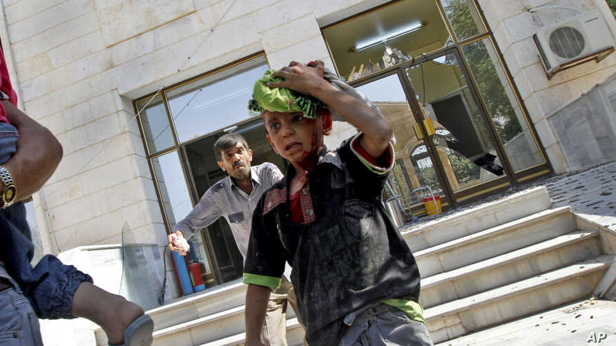 Wounded Syrians evacuate a field hospital after a second air strike in Azaz on the outskirts of Aleppo, Syria, August 15, 2012.