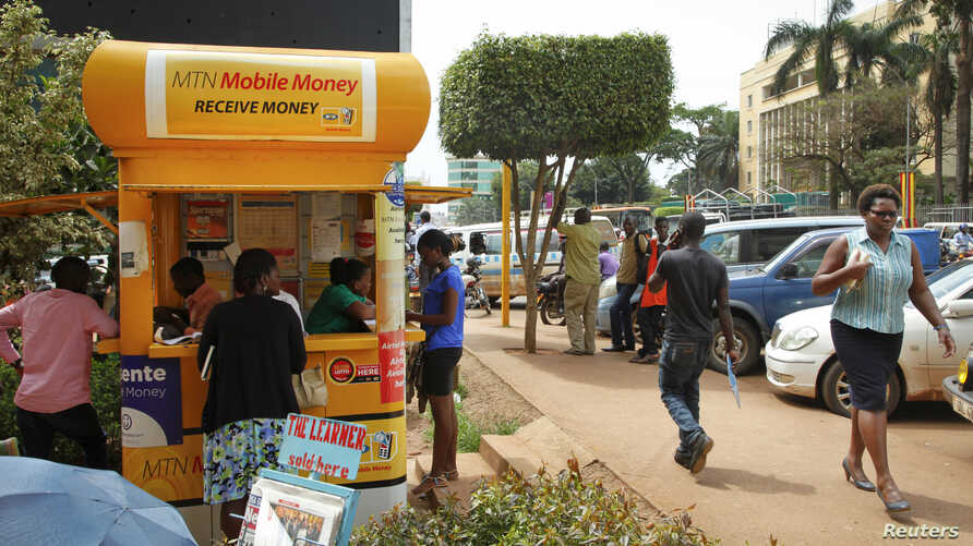 In this photo taken Sept. 29, 2016, Ugandans use a mobile money point in Kampala, Uganda. Mobile money has become a way of life for many Africans.y