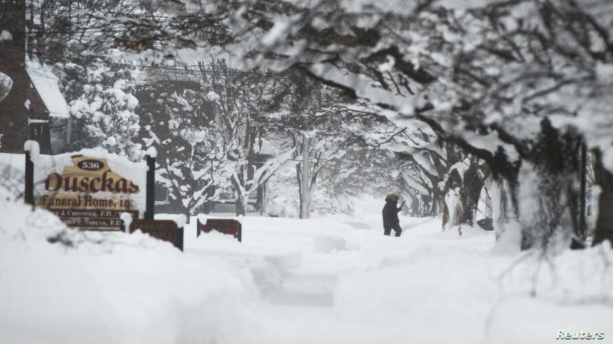 A resident takes a walk on 10th Street after two days of record-breaking snowfall in Erie, Pennsylvania, U.S., Dec. 27, 2017.