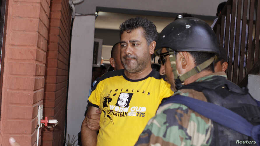 """FILE - Drug lord Jarvis Chimenez Pavao, alias """"Pavao,"""" is escorted to his cell in Asuncion after being arrested in Concepcion, Paraguay, Dec. 27, 2009."""