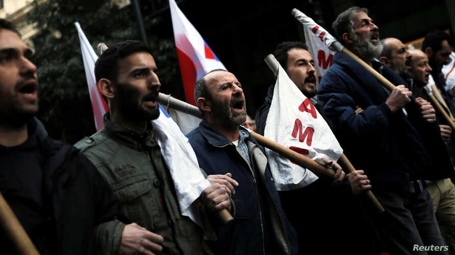 Protesters from the communist-affiliated trade union PAME shout slogans during a demonstration against changes to laws about calling strikes in Athens, Greece, Jan. 9, 2018.