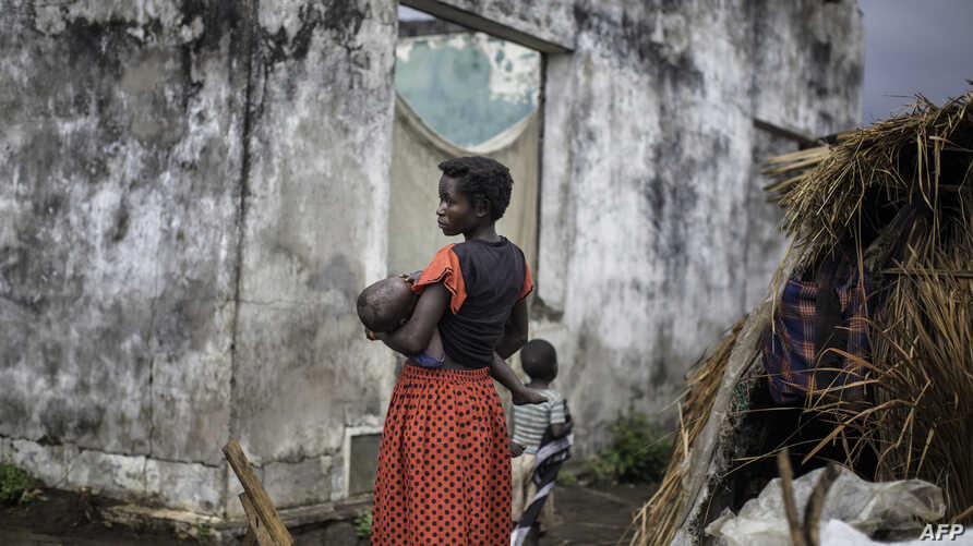 A woman holds her child at a makeshift camp for internally displaced persons (IDPs) among old abandoned buildings in Kalemie, Tanganyika province, Democratic Republic of the Congo, Sept. 18, 2017.