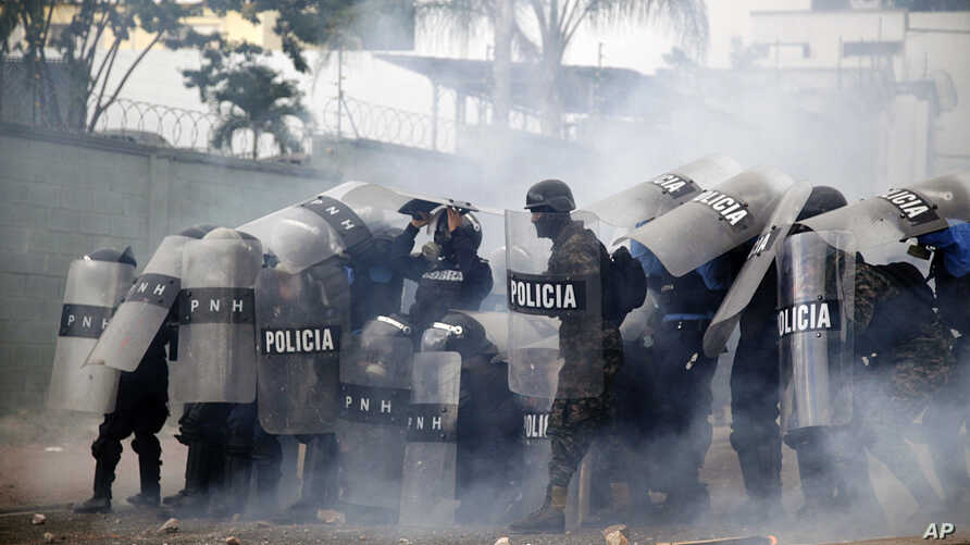 Police stand amid tear gas as they clash with supporters of opposition presidential candidate Salvador Nasralla near the institute where election ballots are stored in Tegucigalpa, Honduras, Nov. 30, 2017.  Protests are growing as incumbent President...