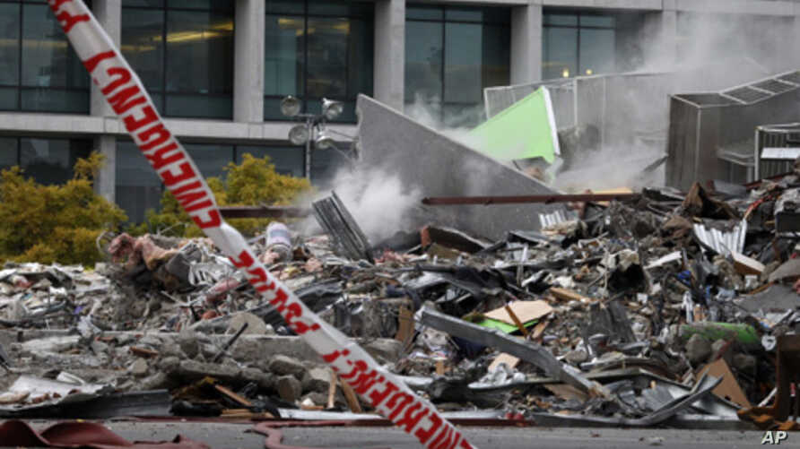 Smoke rises from the collapsed CTV building, that housed a TV broadcaster and an English language school, following Tuesday's earthquake Christchurch, New Zealand, February 23, 2011.