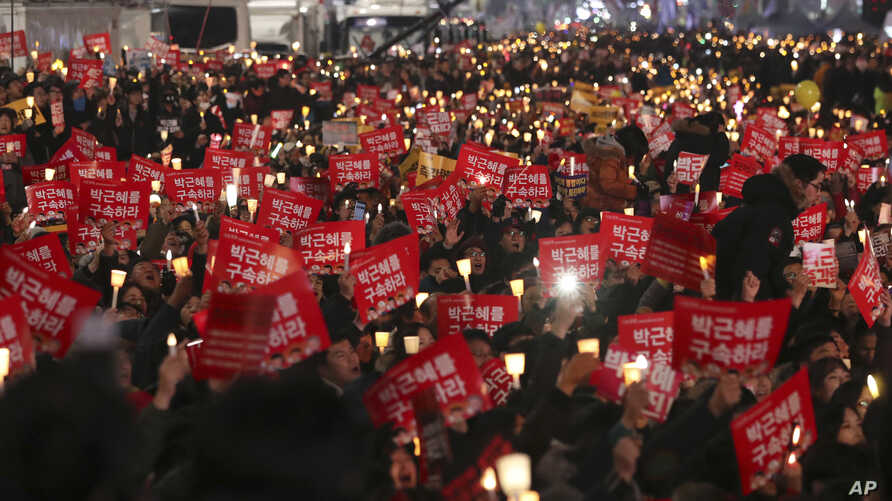 Protesters hold candles near the Gwanghwamun, the main gate of the 14th-century Gyeongbok Palace, one of South Korea's well known landmarks, during a rally calling for South Korean President Park Geun-hye to step down in Seoul, South Korea, Saturday,
