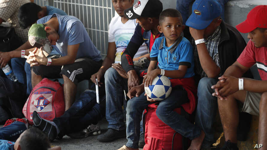 FILE - A Honduran boy holds his soccer ball after receiving a processing bracelet from a worker of the Mexican Migration Institute or Instituto Mexicano de Migracion, as he enters Mexico from Guatemala, near Ciudad Hidalgo, Chiapas State, Mexico, Jan