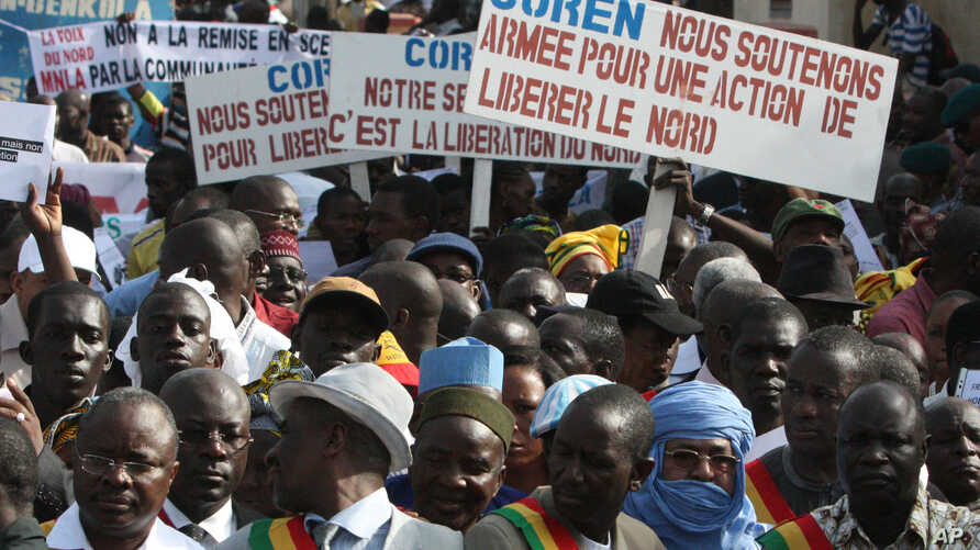 People originally from northern Mali carry signs reading 'We support army action to liberate the North,' as thousands of Malians, including elected officials, front, marched in support of foreign aid and military intervention to retake Mali's north f