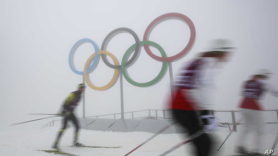 Cross-country skiers train in front of the olympic rings at the Laura biathlon and cross-country ski center, at the 2014 Winter Olympics, Monday, Feb. 17, 2014.