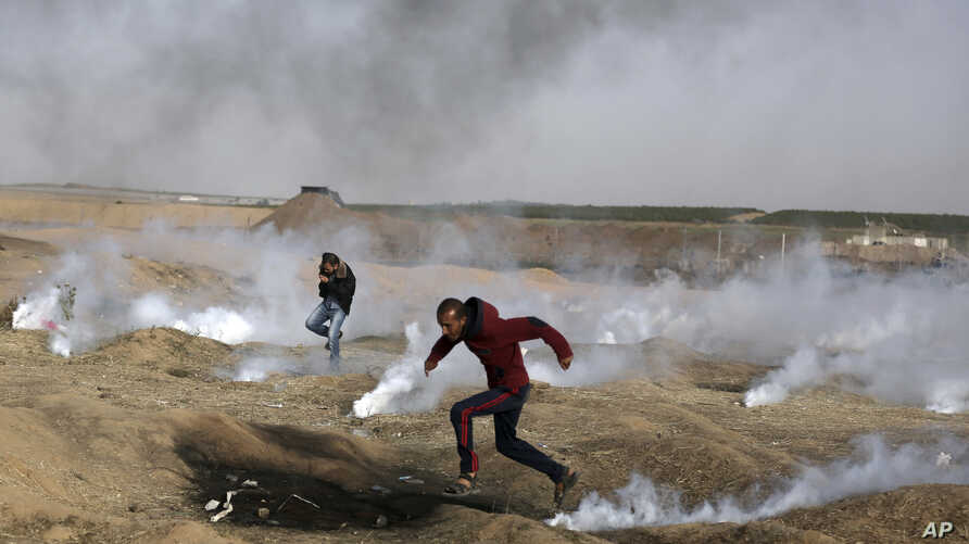 Palestinian protesters run for cover from teargas fired by Israeli troops during a protest at the Gaza Strip's border with Israel, April 13, 2018.