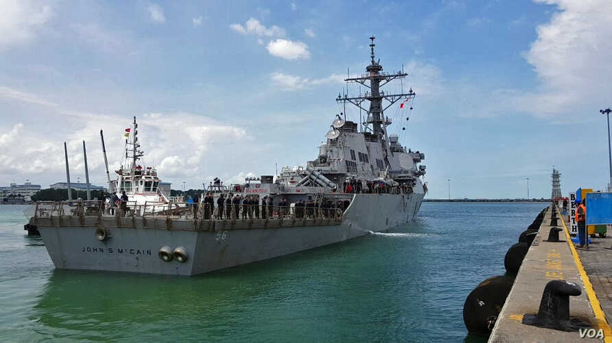 The guided-missile destroyer USS John S. McCain (DDG 56) arrives pier side at Changi Naval Base, Republic of Singapore following a collision with the merchant vessel Alnic MC while underway east of the Straits of Malacca and Singapore.