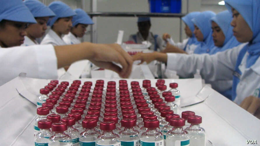 Lab workers in the Bandung BioFarma facility in Indonesia examine vials that have vaccine vial monitor technology incorporated into their labels, in Bandung, Indonesia, February 2017. (U. Kartoglu/PATH)