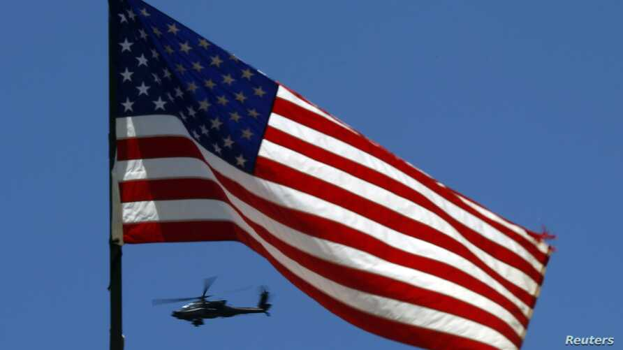 U.S. Army Apache helicopter flies past a flag on Observation Post Mustang in Afghanistan's Kunar Province, June 4, 2012 file photo.