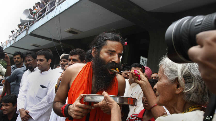 An old Indian woman offers food to yoga guru Baba Ramdev to break his fast in New Delhi, India, Aug. 14, 2012.