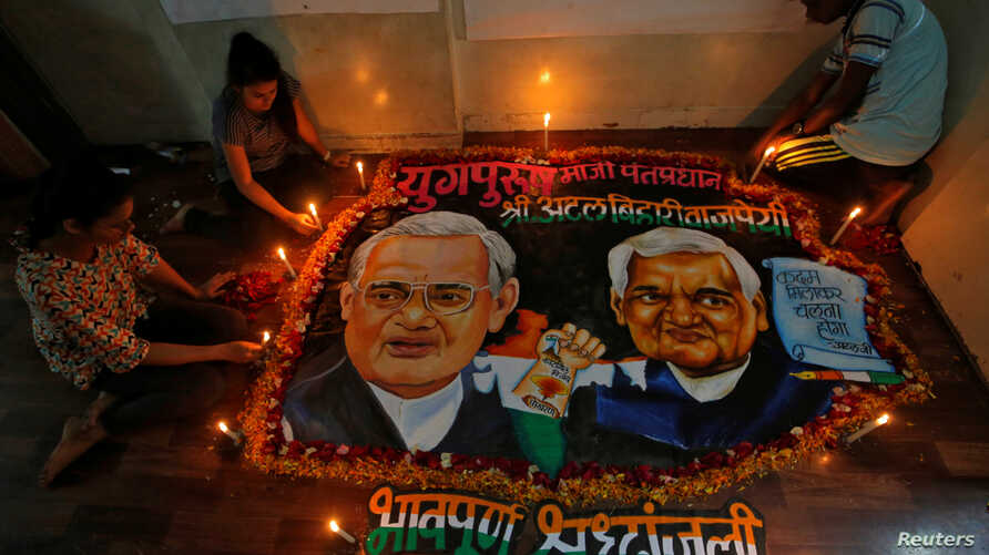 Students place candles around a painting featuring India's former prime minister Atal Bihari Vajpayee to pay him homage in Mumbai, India, Aug. 16, 2018.